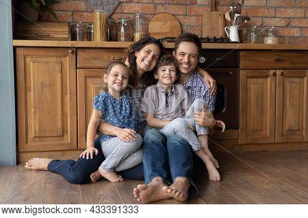 Bonding Smiling Parents Cuddling Little Kids Siblings At Home.