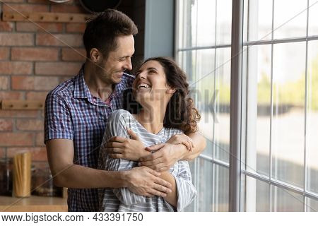 Affectionate Happy Young Man Cuddling Smiling Attractive Wife.