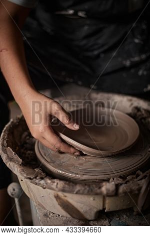 Hands Of Craftsman Artist Working On Pottery Wheel.