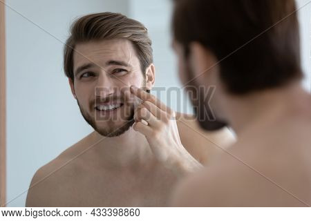 Man Looking In Mirror Touch Face With Pimple On Cheekbone
