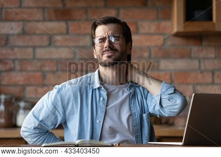 Tired Man In Glasses Rubbing Stiff Neck Muscles, Feeling Pain