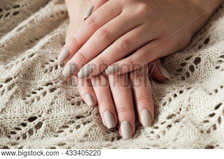 Matt Nude Beige Nails Close Up. Winter Or Autumn Manicure, Woman Hand On Warm Sweater