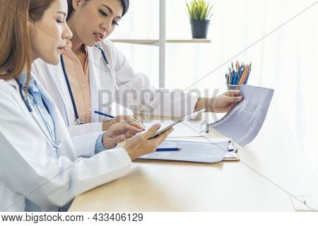 Young Asian Woman Doctor Meeting At Office Table. Two Women Doctors Discussing Diagnosis Meeting In