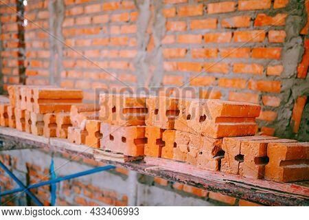 Focus On The Orange Bricks Within The Construction Site Where Construction. The Orange Bricks Are St