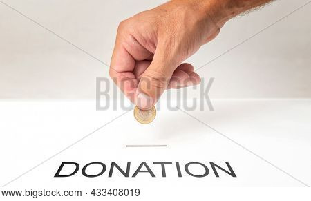 Man hand putting coin into donation box