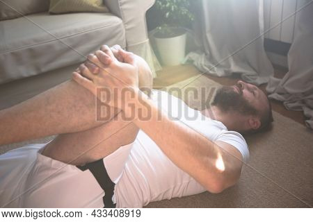 Mid Adult Mature Man In White Sport Clothes Practice Yoga Stretch Doing Exercise At Home Minimalisti