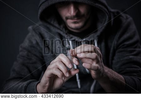 A Drug Addicted Person Draws A Dose Of The Drug In A Syringe. The Guy Is An Addict, The Concept Of T