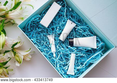 A Set Of Samples Of Different Cosmetics For Face And Body Care In A Box With Blue Shavings. Online S