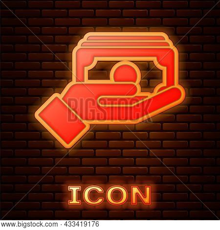 Glowing Neon Stacks Paper Money Cash In Hand Icon Isolated On Brick Wall Background. Insurance Conce