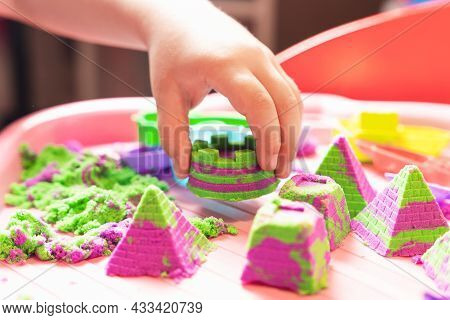 The Child Sculpts Figures From Multi-colored Kinetic Sand, Developing Fine Motor Skills Of Hands.