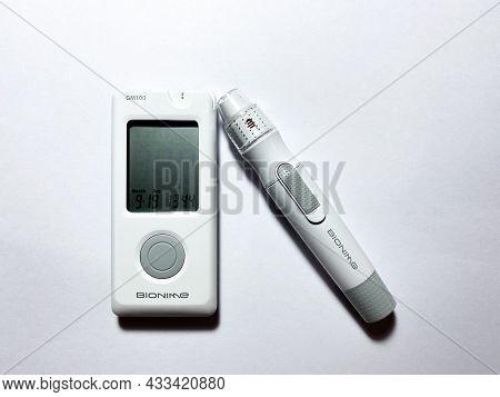 Grodno, Belarus - 09.19.2021: Bionime Blood Glucose Meter And A Pen For Finger Piercing. Glucose Mea