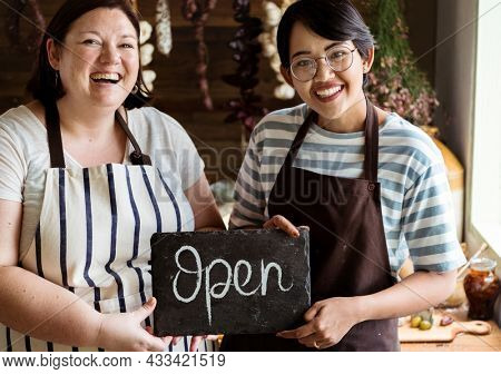 Cheerful deli shop owners showing an open sign