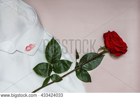 A Trace Of Lipstick Lips From A Kiss On Men's Clothing. One Red Rose Lies On A White Shirt On A Pink