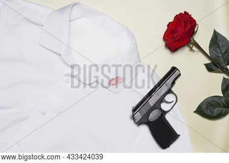 A Trace Of Lipstick Lips From A Kiss On Men's Clothing. One Red Rose With A Black Gun Is Lying On A