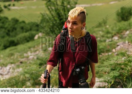 Young Woman With Androgynous Features Hiking With A Camera In The Picos De Europa National Park.