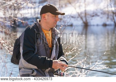 A Fisherman With A Fishing Rod And A Backpack Catches Fish On The Bank Of A Snow-covered River In Ea