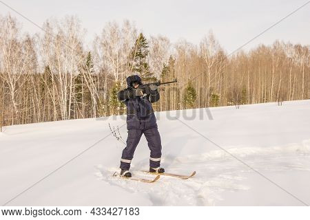 A Hunter Or Poacher Stands On Skis At The Edge Of The Forest And Aims An Automatic Weapon At Prey Or