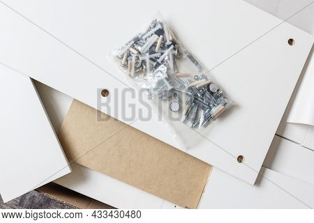 Opened Box With Furniture Assembly Parts And Tools On The Floor. Self Assembling And Diy Furniture A