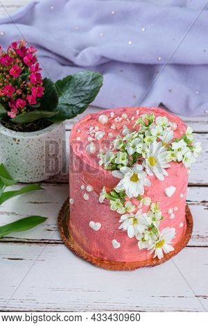 Chocolate Cake Covered With Pink Butter Cream. Decorated With White Hearts, Pearls And Flowers. In T