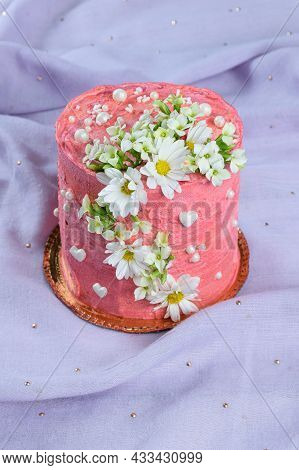 Chocolate Cake Covered With Pink Butter Cream. Decorated With White Hearts, Pearls And Flowers. On A