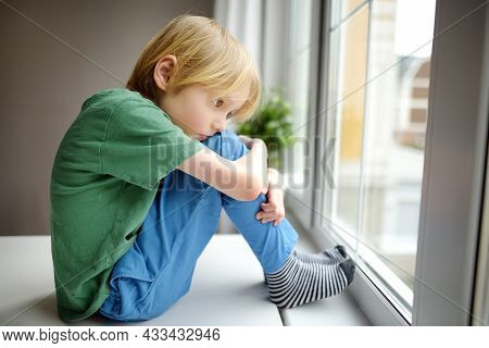 Sad Little Boy Sitting Near Window And Watching Street. Lonely At Home. No Friends, No Siblings. One