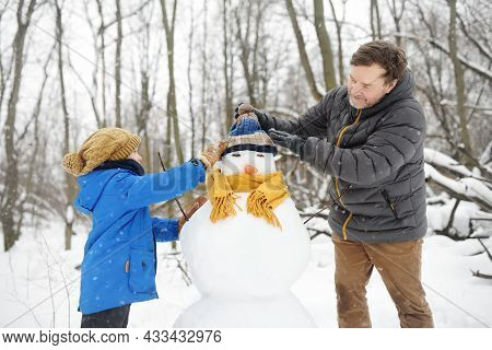 Little Boy With His Father Building Snowman In Snowy Park. Dad And Son Tied A Scarf For Snowman. Act