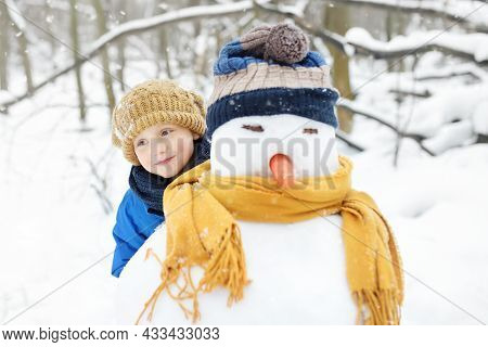 Little Boy Building Snowman In Snowy Park. Child Embracing Snowman Wearing Hat And Scarf. Active Out