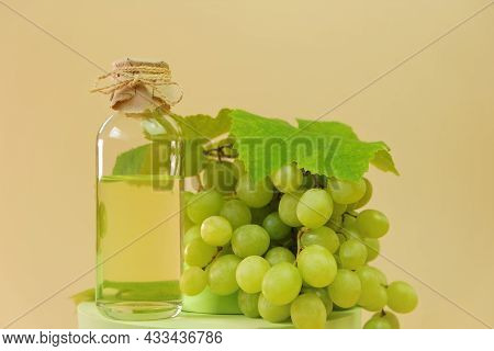 Grape Seed Oil.bottle And Bunch Of Green Grapes On Podium On A Beige Background. Organic Natural Bio