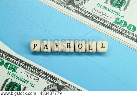 Banknotes With The Word Payroll On Small Wooden Cubes