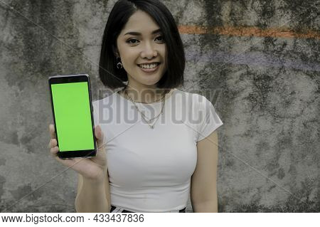 Happy And Smile Young Asian Women Showing Green Blank Screen.