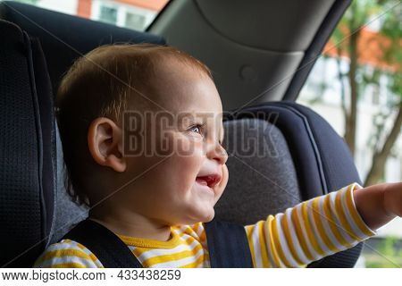 Happy Caucasian Baby Boy In Yellow Striped T-shirt Sitting In Grey Car Seat And Smiling. Road Trips