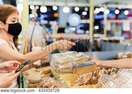 Female Customer In Protective Mask Make Contactless Mobile Payment Sales Woman In Retail Shop