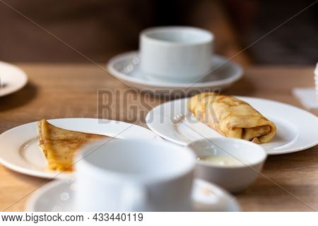 Fresh Pancakes With Filling On The Table Next To White Mugs For Coffee Or Tea For Breakfast. Pancake
