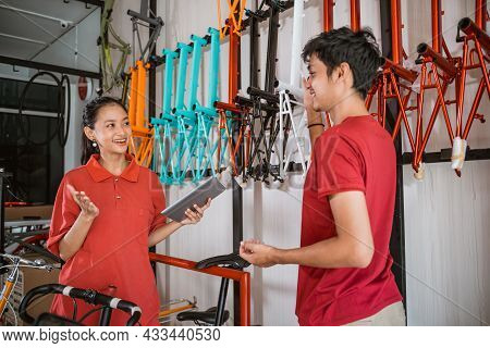 A Woman Holding A Pad Chats With A Male Shop Assistant While Arranging A Bicycle Frame