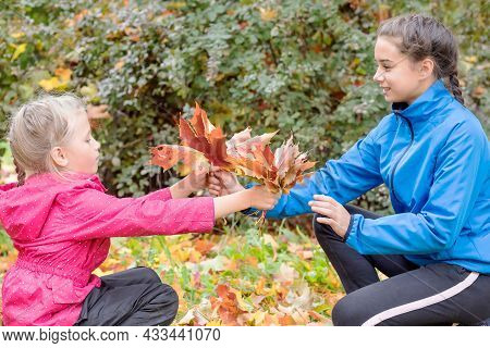 Two Funny Girls Sisters On A Walk In The Park Collected Colorful Autumn Leaves.