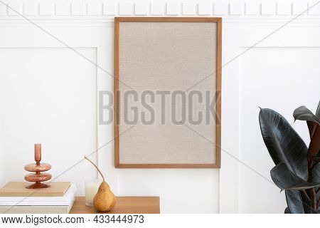 Picture frame hanging over a wooden sideboard table
