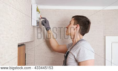 Professional Electrician In Jumpsuit Presses Levers On Contemporary Switchboard To Fix Above Front D
