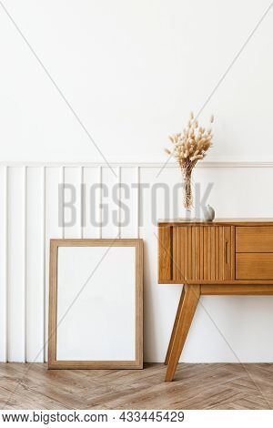 Picture frame by a wooden sideboard table
