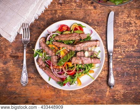 Delicious Salad With Vegetables And Pieces Of Beef Steak On The Table, Portion With Fork And Knife,
