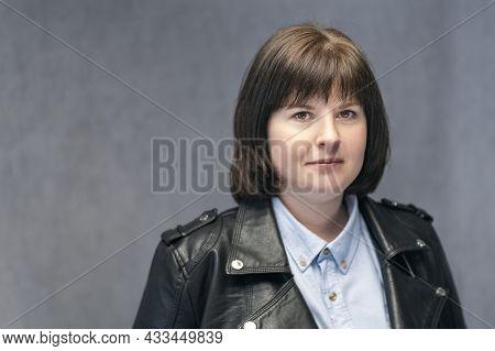 Portrait Of Young Confident Woman With Bob Haircut In Leather Jacket. Brunette Girl With Round Face