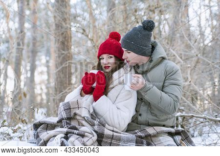 Young Couple In Love In Winter Park Wrapped Themselves In Blanket And Drinks Tea. Love Story.