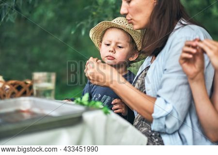 Young Mother And Little Son In Straw Hat With Food Sit At Table During Picnic In Green Park On Nice