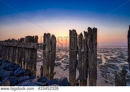 View Of The Sea During Sunset, At Low Tide. A Colorful Dramatic Sky. Wooden Posts As A Silhouette In