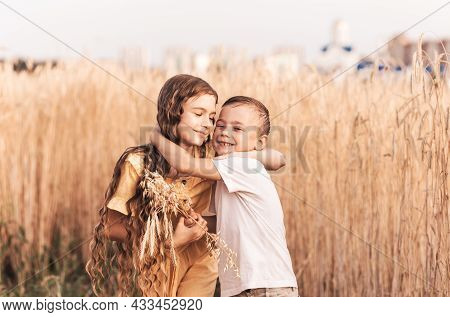 Older Sister Walks With Her Brother In Nature In The Summer. Happy Kids Sibling Walking And Playing.