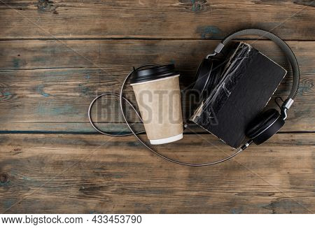 old book with headphone and a cup of coffee in a disposable paper cup on a wooden table. Remote education concept. Top view