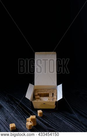 Refined Brown Sugar In Dense Cubes In A Cardboard Box On A Black Background