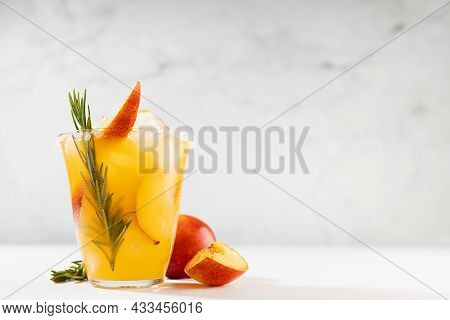 Refreshing Juicy Peach Cocktail With Ice, Rosemary, Sugar Rim, Fruit Slices In Misted Glass, Ingredi