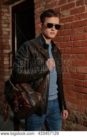 Lifestyle. Portrait of a confident and stylish young man in sunglasses, a leather jacket and trendy leather bag standing by a brick wall. Men's leather and casual clothing style.