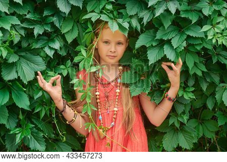 Portrait of a beautiful girl child dressed in hippie style standing outdoor among the leaves of wild grapes. Kid's fashion.