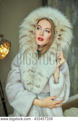 Portrait of an amusing blonde woman in an expensive mink and lynx fur coat. Luxury classic interior of  an apartment. Fur coat fashion.